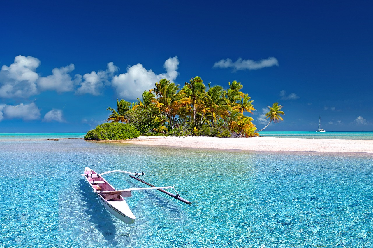 white sand island with coconut trees sorounded with clear water beach with a floating canoe