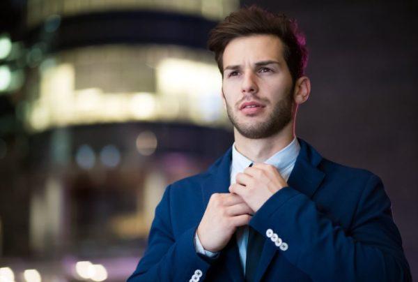 guy in suit fixing his tie